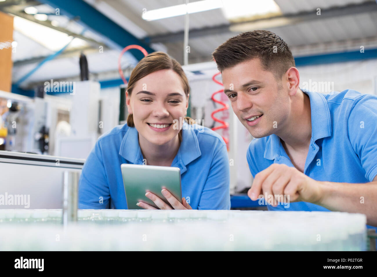 Engineer And Apprentice With Digital Tablet Working In Bottle Capping Factory - Stock Image