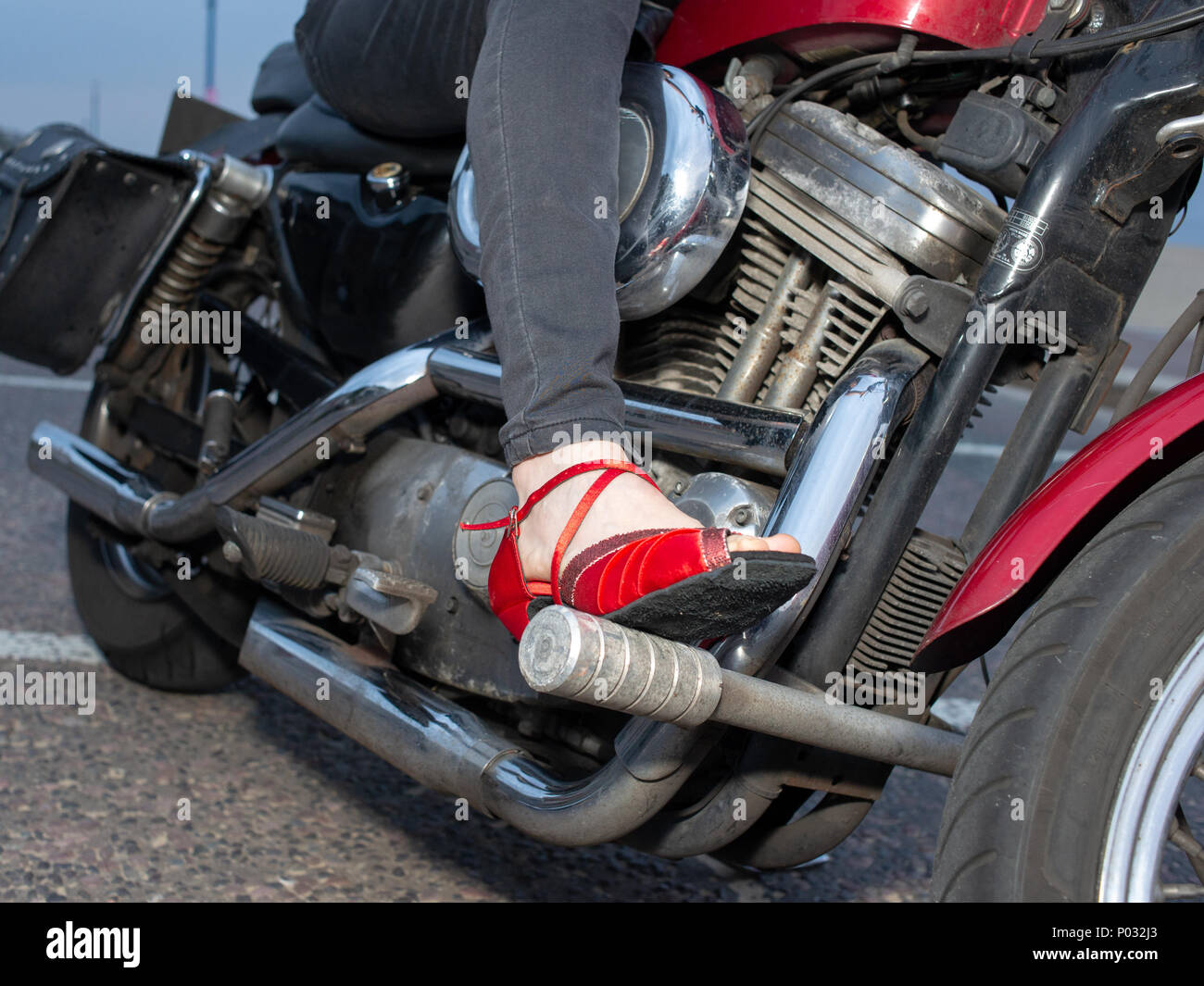 Woman's foot in red high heeled shoes sitting on a motorbike. - Stock Image