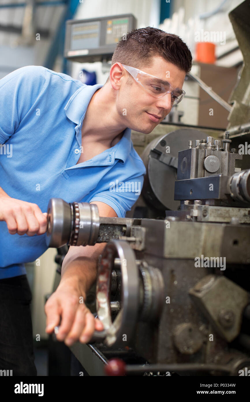 Male Engineer Operating Lathe In Factory - Stock Image