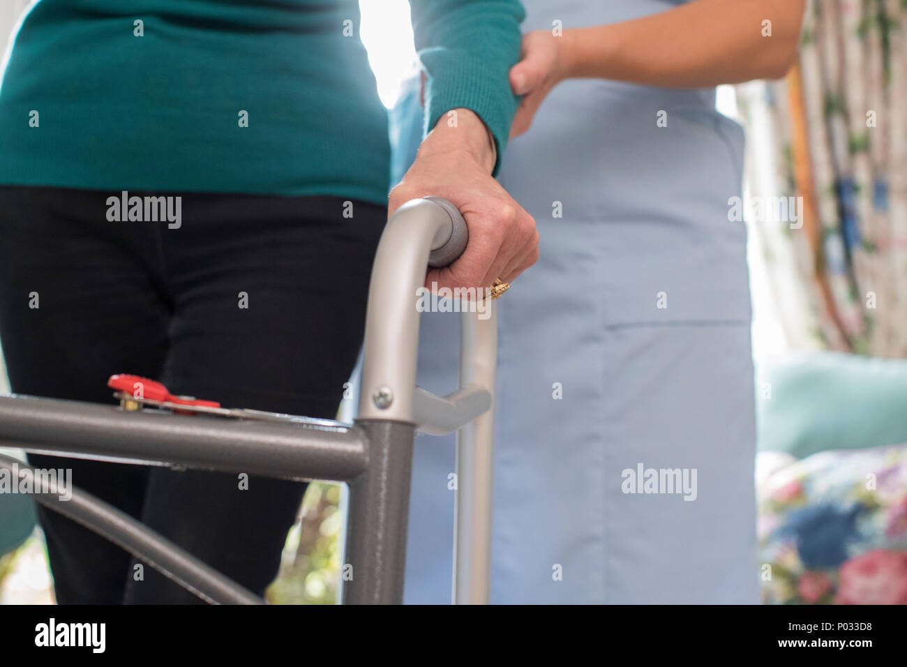 Senior Womans Hands On Walking Frame With Care Worker In Background - Stock Image