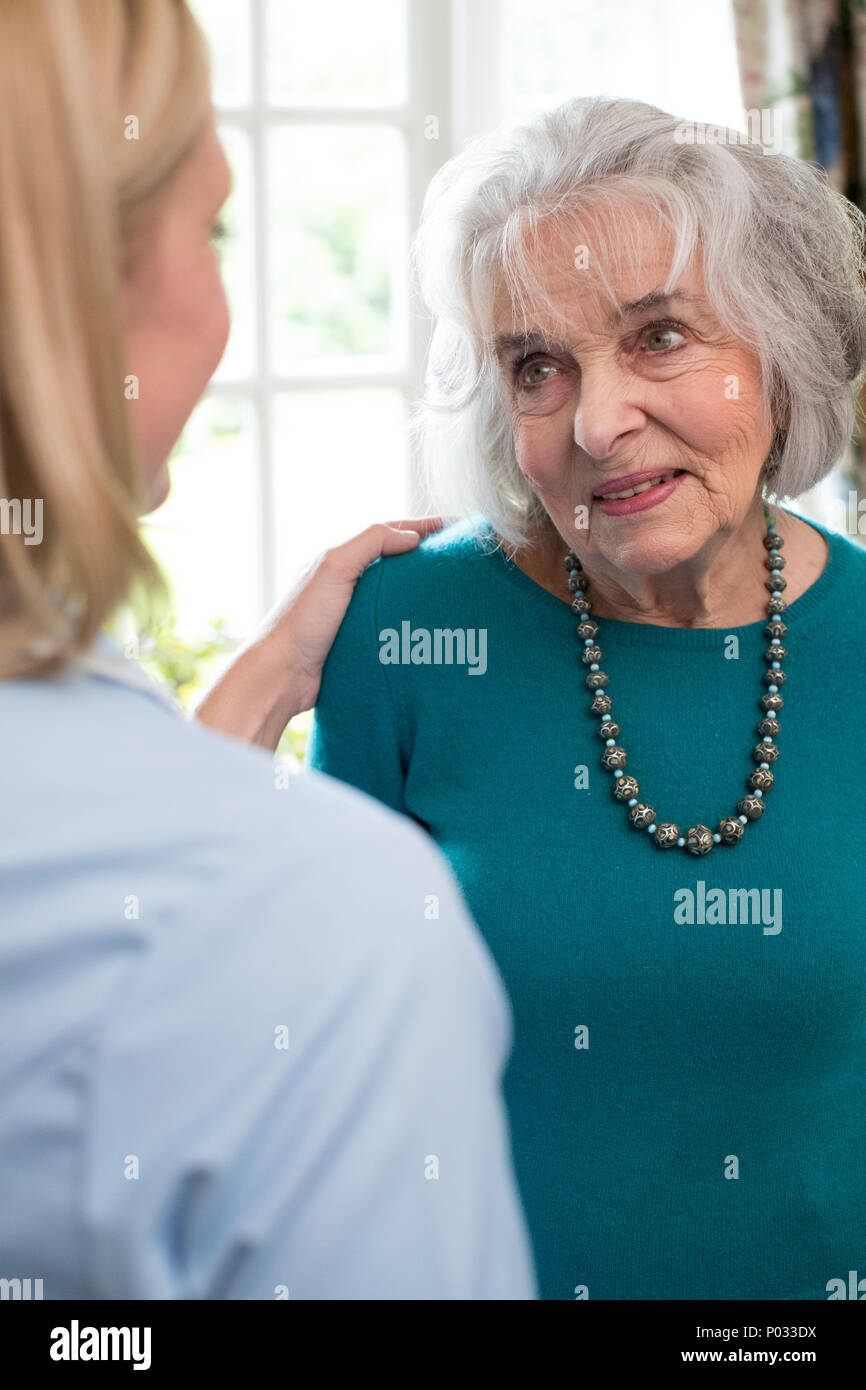 Care Worker Talking To Senior Woman At Home Stock Photo