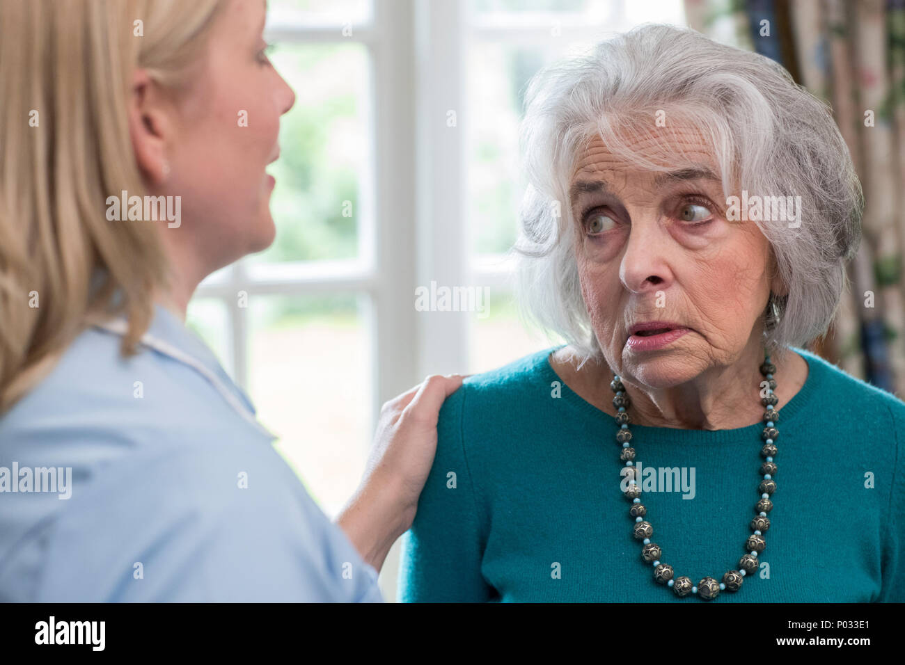Care Worker Talking To Depressed Senior Woman At Home - Stock Image