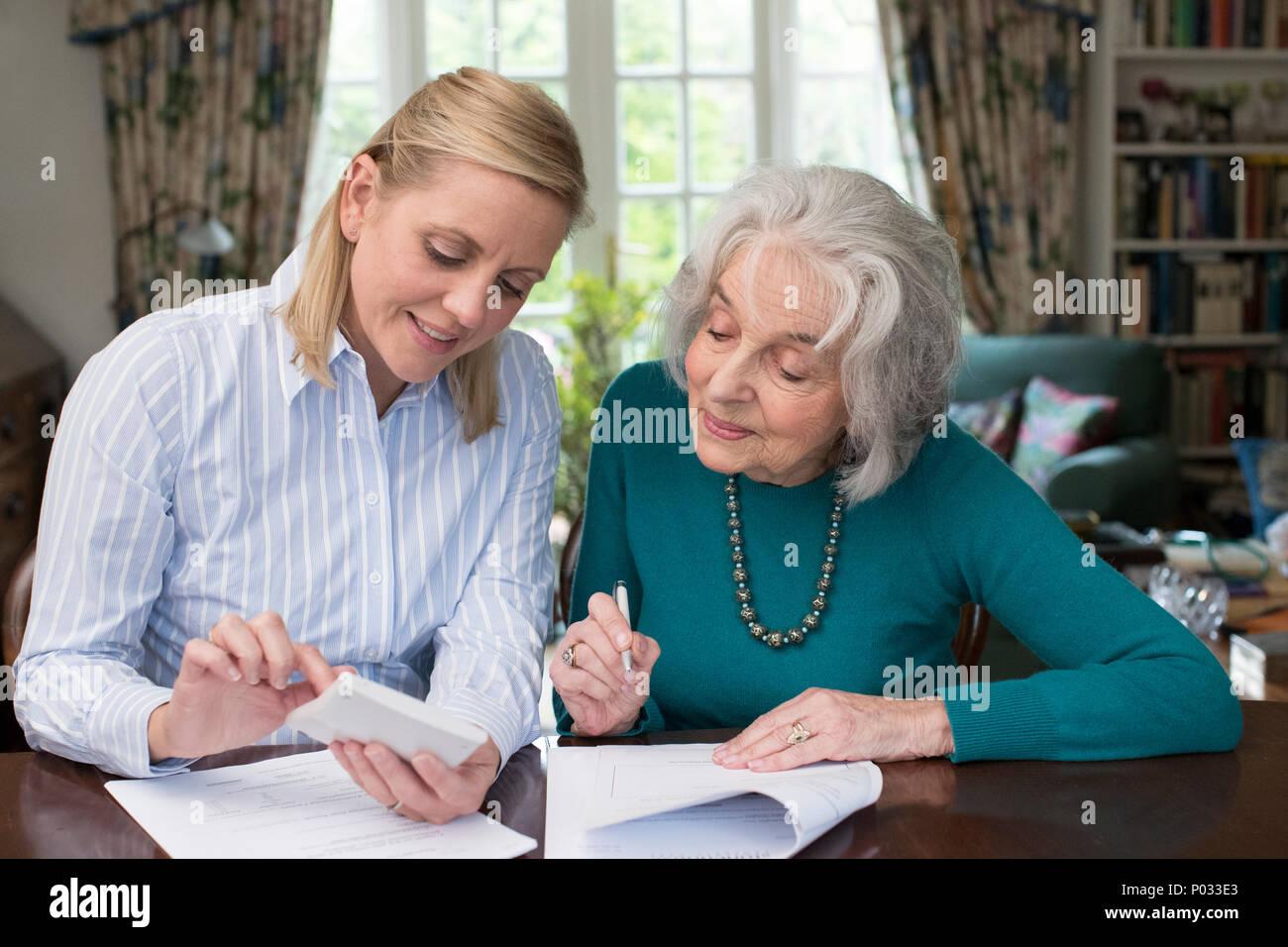 Woman Helping Senior Neighbor With Paperwork - Stock Image