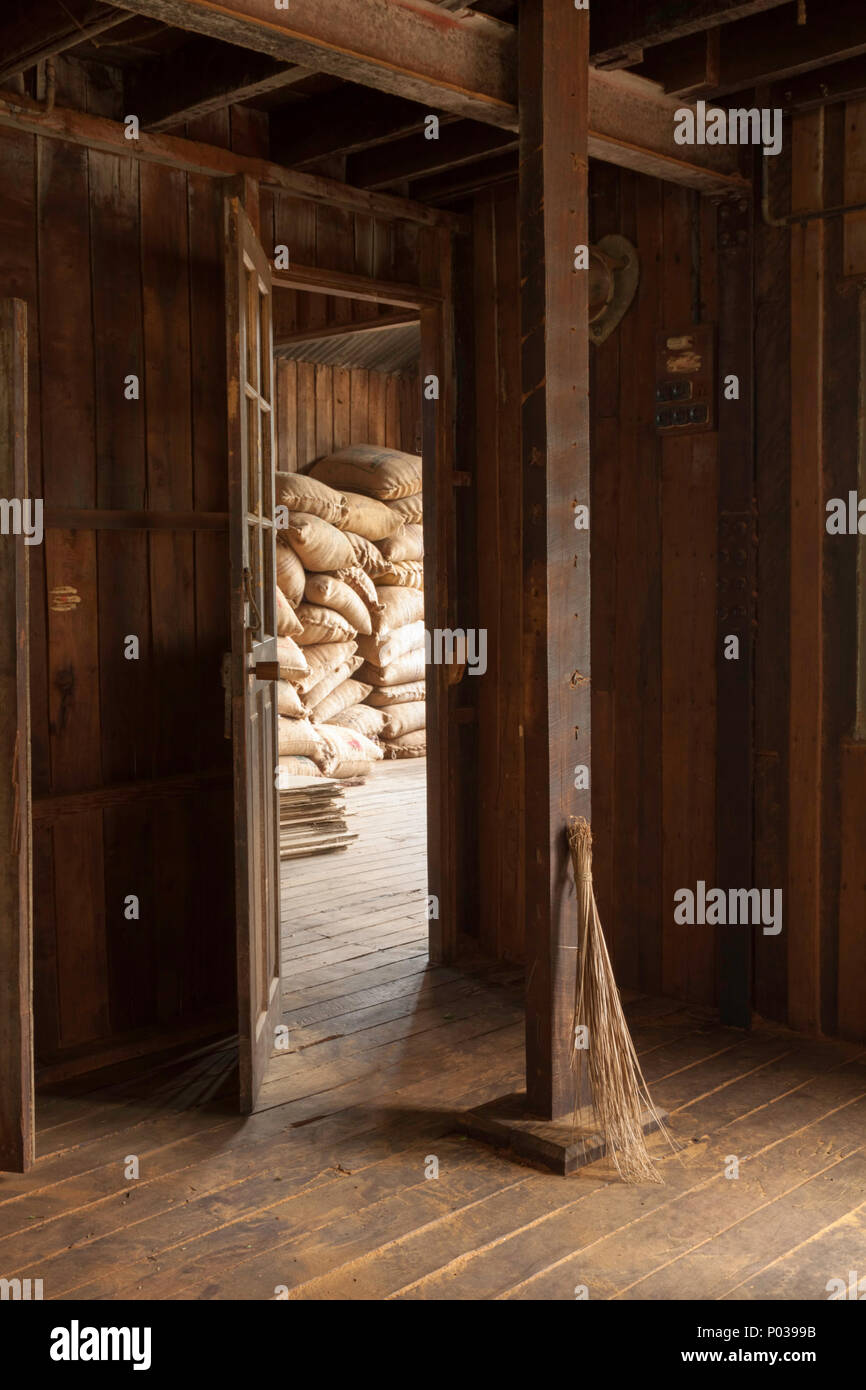 Old brush propped up against a wooden beam in the atmospheric Kolukkumalai tea factory, Kerala, India. Sacks of tea are piled up through the doorway. - Stock Image