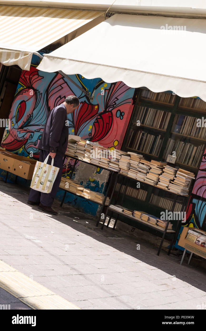 Man shopping outside 2nd hand book shop stall, Athens, Greece. - Stock Image