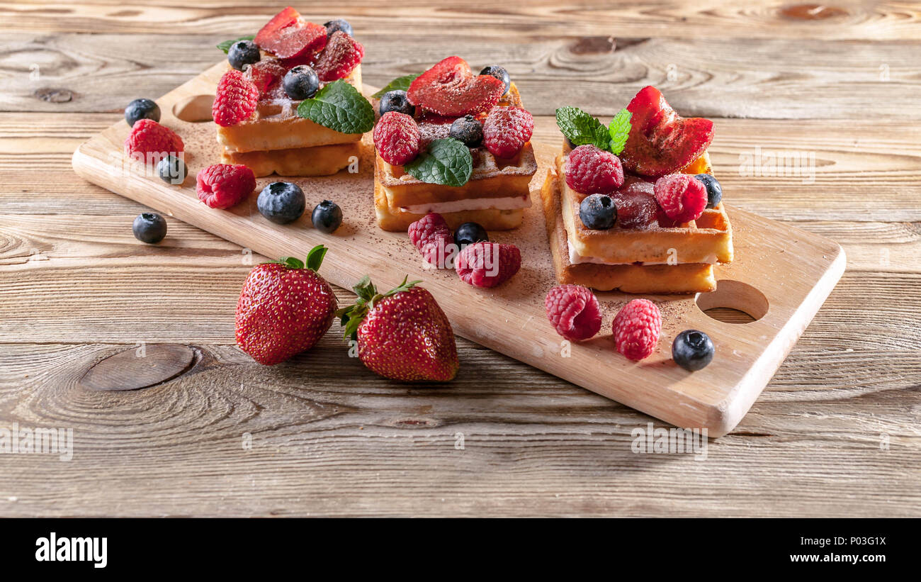 Viennese waffles with strawberry jam, fresh strawberries, raspberries, blueberries and chocolate chips on a wooden table. Delicious breakfast concept - Stock Image