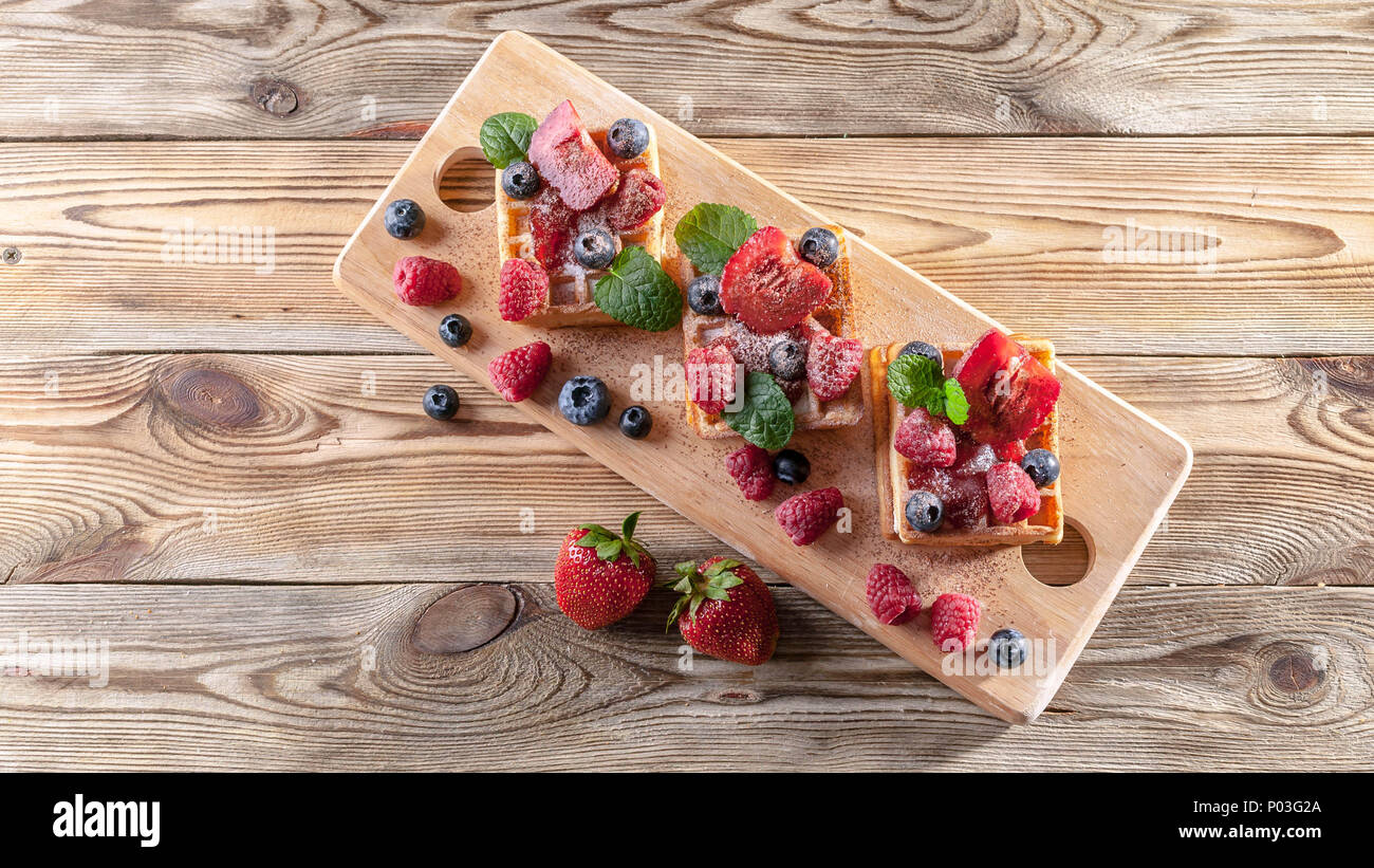 Belgian waffles with strawberry jam, fresh strawberries, raspberries, blueberries and chocolate chips on a wooden table. Homemade baking. Delicious br - Stock Image
