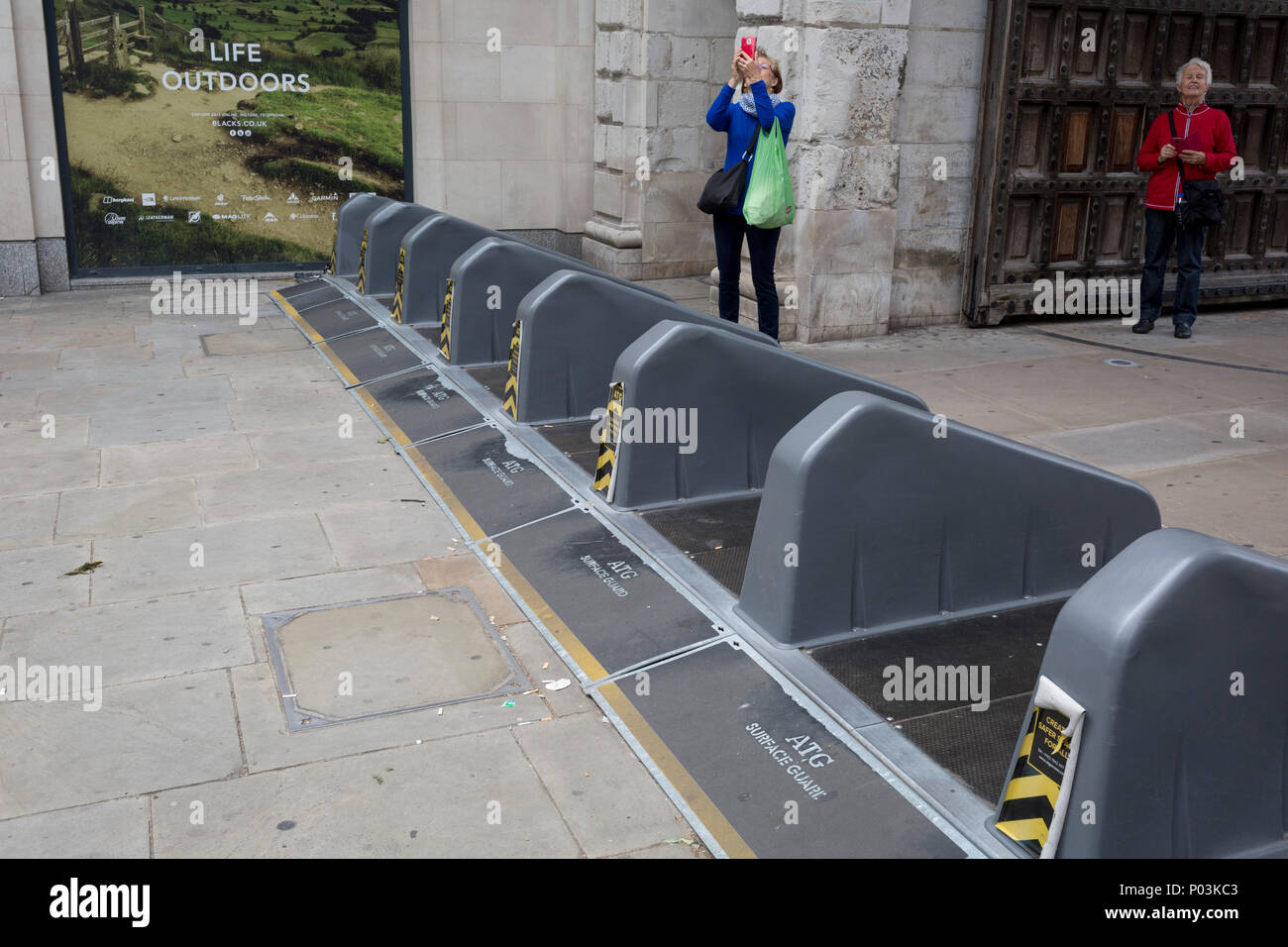 Pedestrians walk over security barriers at one of the entrances to Paternoster Square in the City of London - the capital's financial district, on 4th June 2018, in London, England. Stock Photo