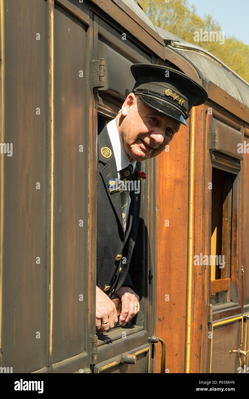 Portrait close up of gentleman ticket inspector on Severn Valley Railway, leaning out of carriage window in the sunshine, ready to greet passengers. - Stock Image