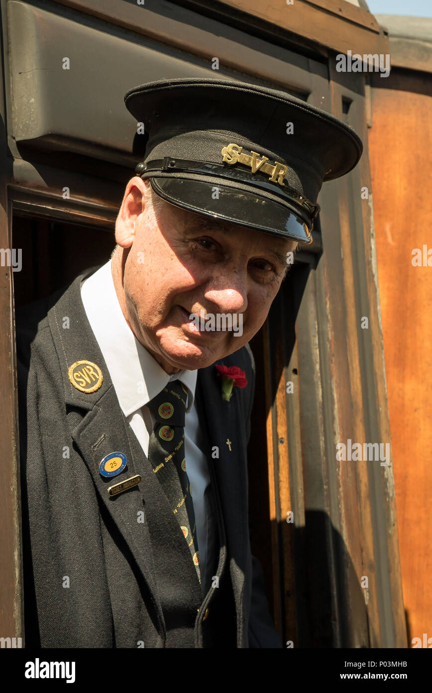 Tight close up of a gentleman ticket inspector on Severn Valley Railway. He leans out of a carriage window greeting passengers waiting on the platform. - Stock Image
