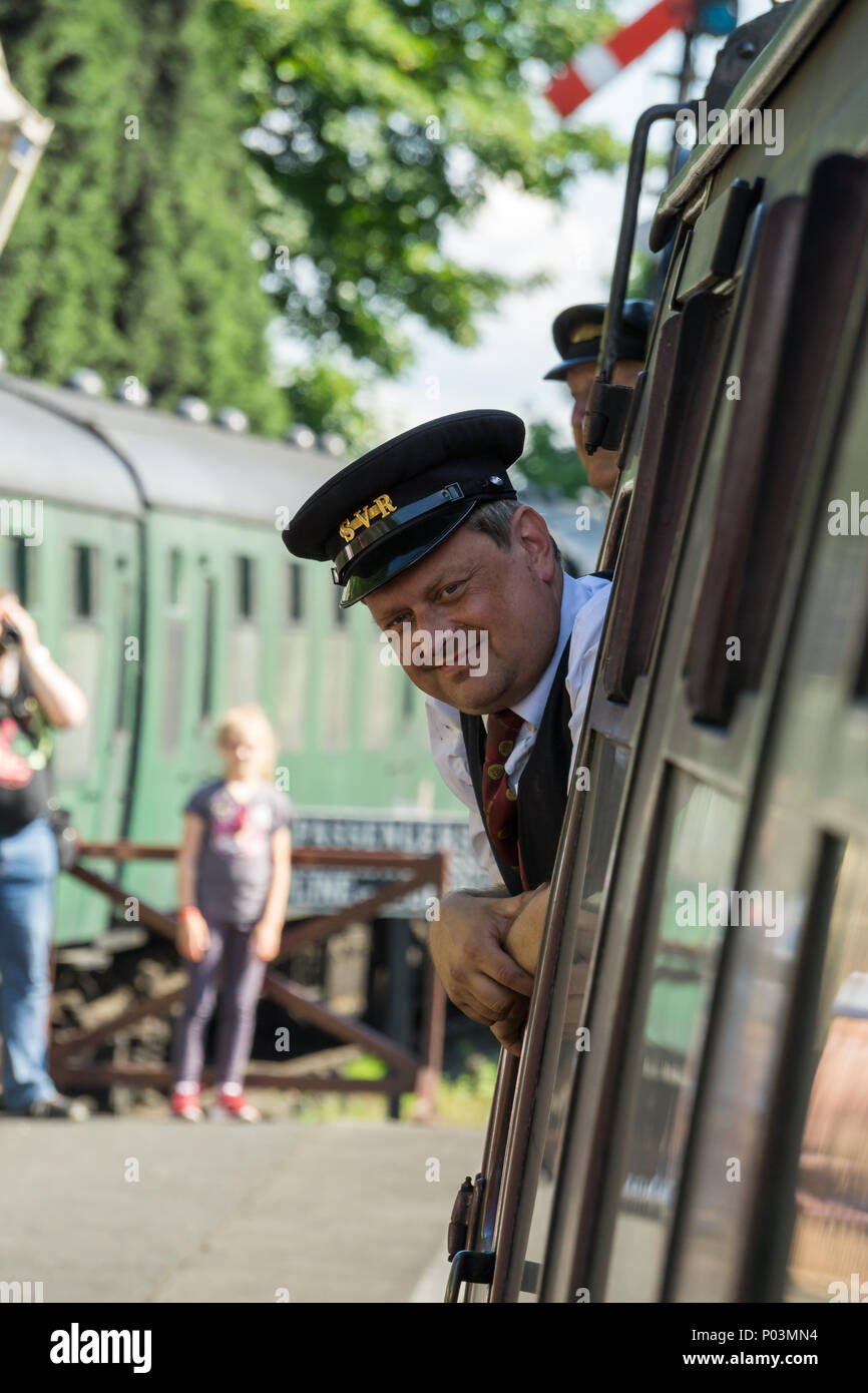 Severn Valley Railway, popular heritage line in Midlands. Guard checks platform as train leaves station. Tourists watch & snap photos in background. - Stock Image