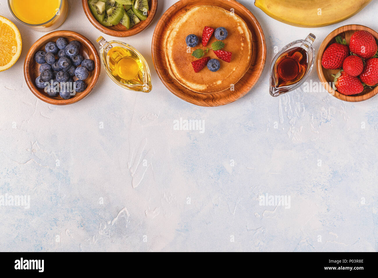 Pancakes with fruit, honey, maple syrup. Top view. - Stock Image