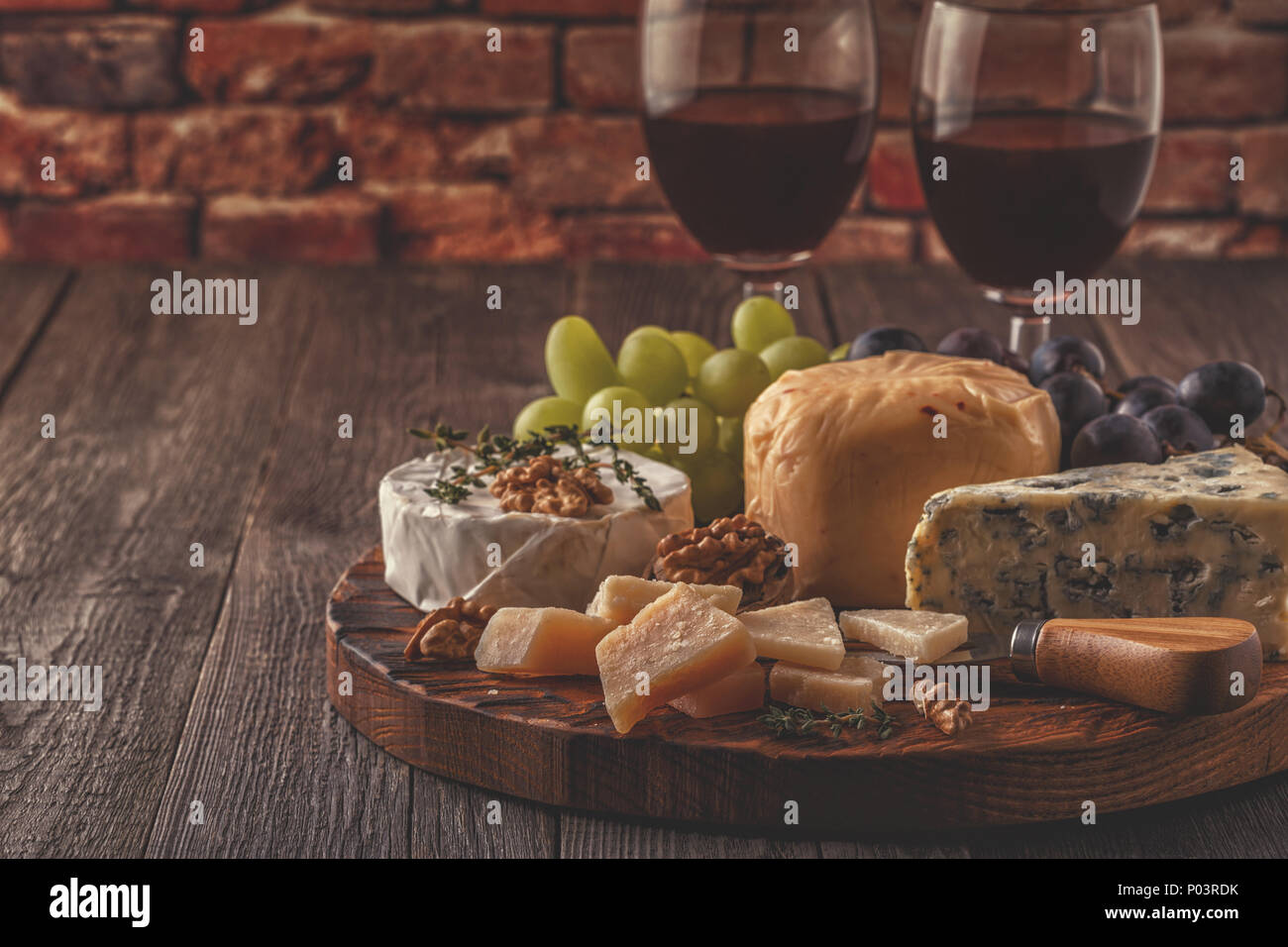 Cheese, nuts, grapes and red wine on wooden background, selective focus. - Stock Image