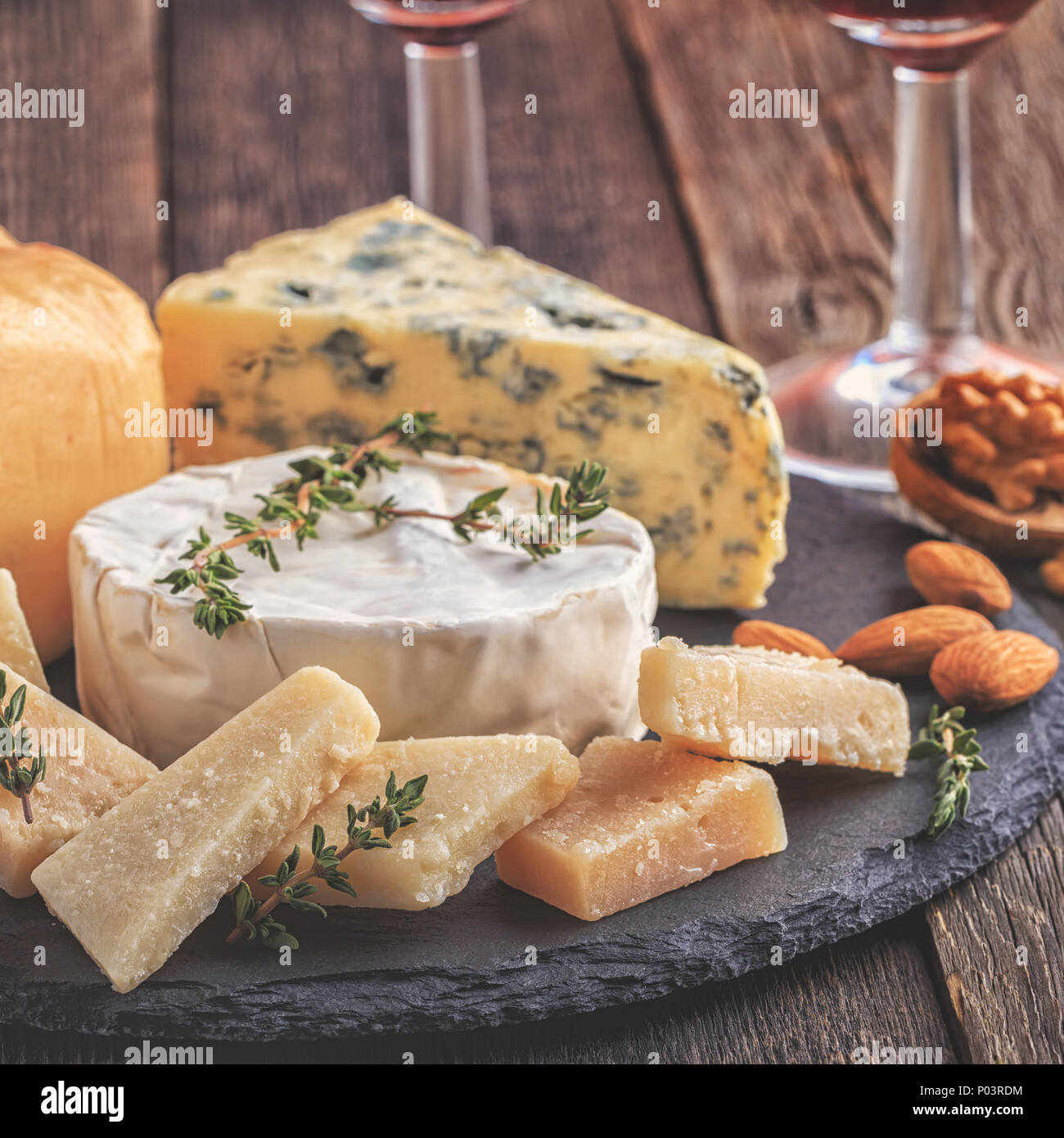 Cheese, nuts, honey and red wine on wooden background, selective focus. - Stock Image
