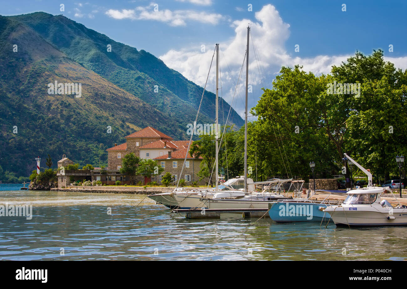 Yacht, house with red roof and boats near pier before storm, Kotor, Montenegro - Stock Image