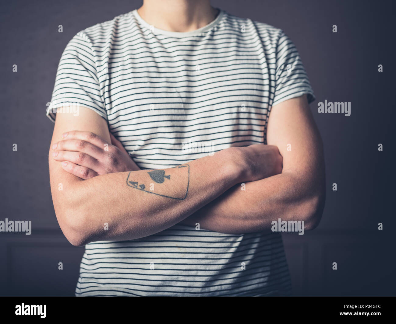 A young man with a tattoo is crossing his arms Stock Photo ... 18f4c852f3c3