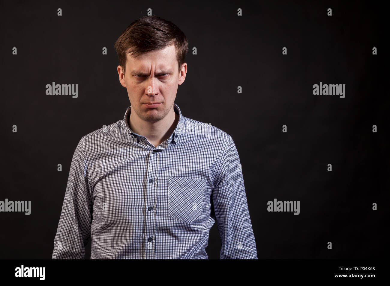 A dark haired white man with distrust expression face knit the brows in a plaid shirt and jeans on a black isolated background - Stock Image