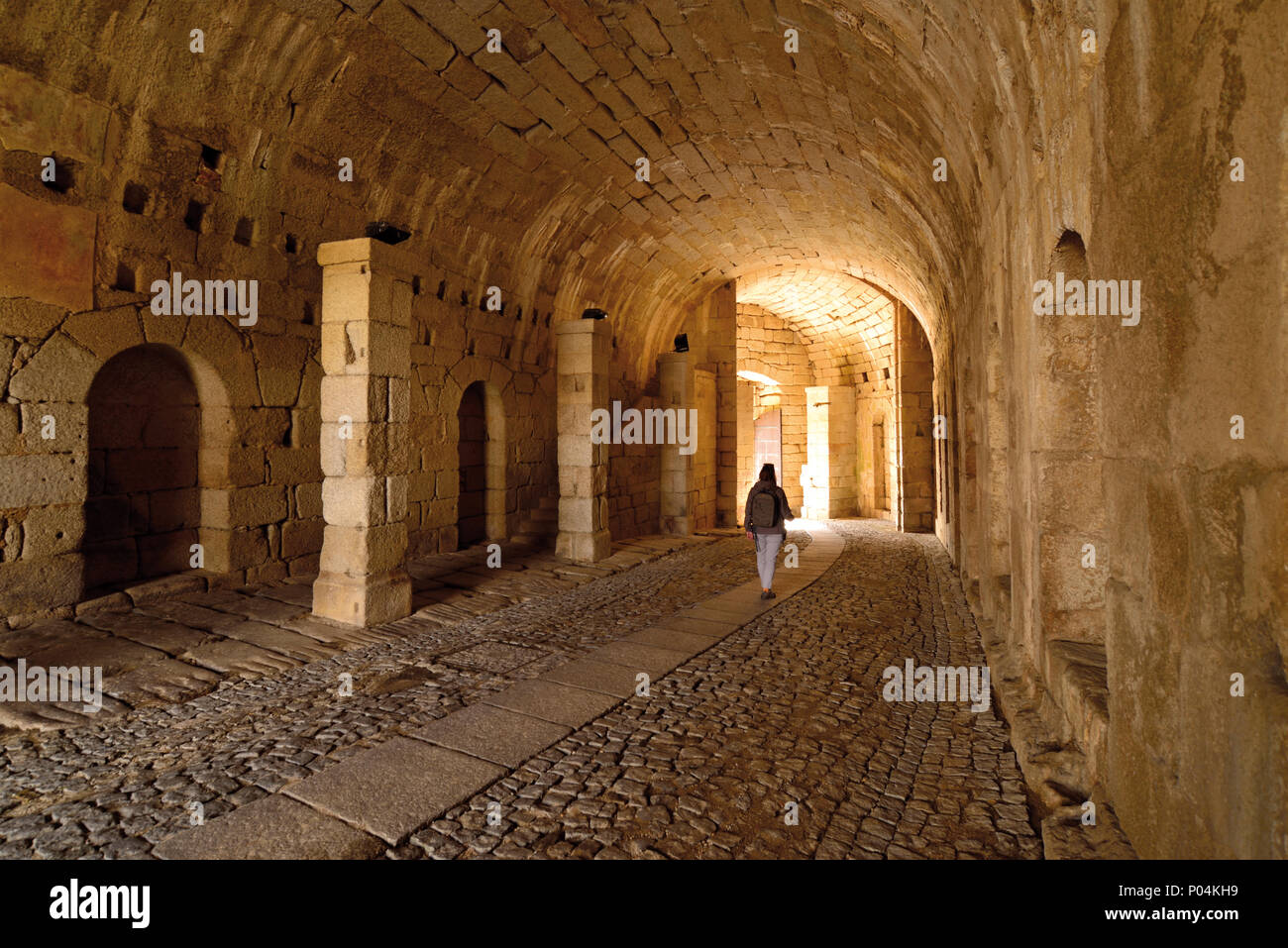 Woman walking in a fortified tunnel towards exit - Stock Image