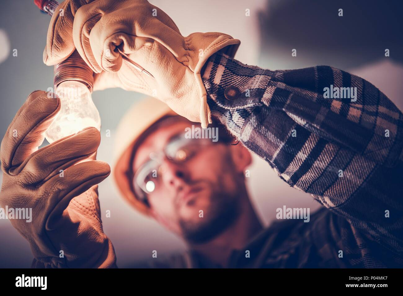 Electrician Fixing the Light Inside Remodeled Apartment. Construction Theme. - Stock Image