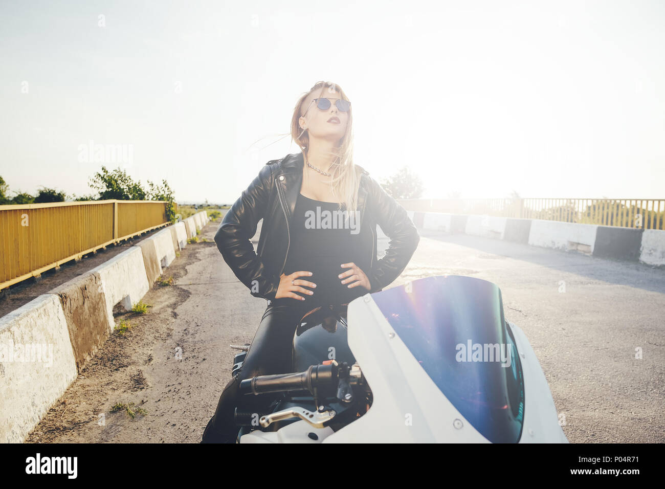 Biker woman looking interested to the sky  - Stock Image