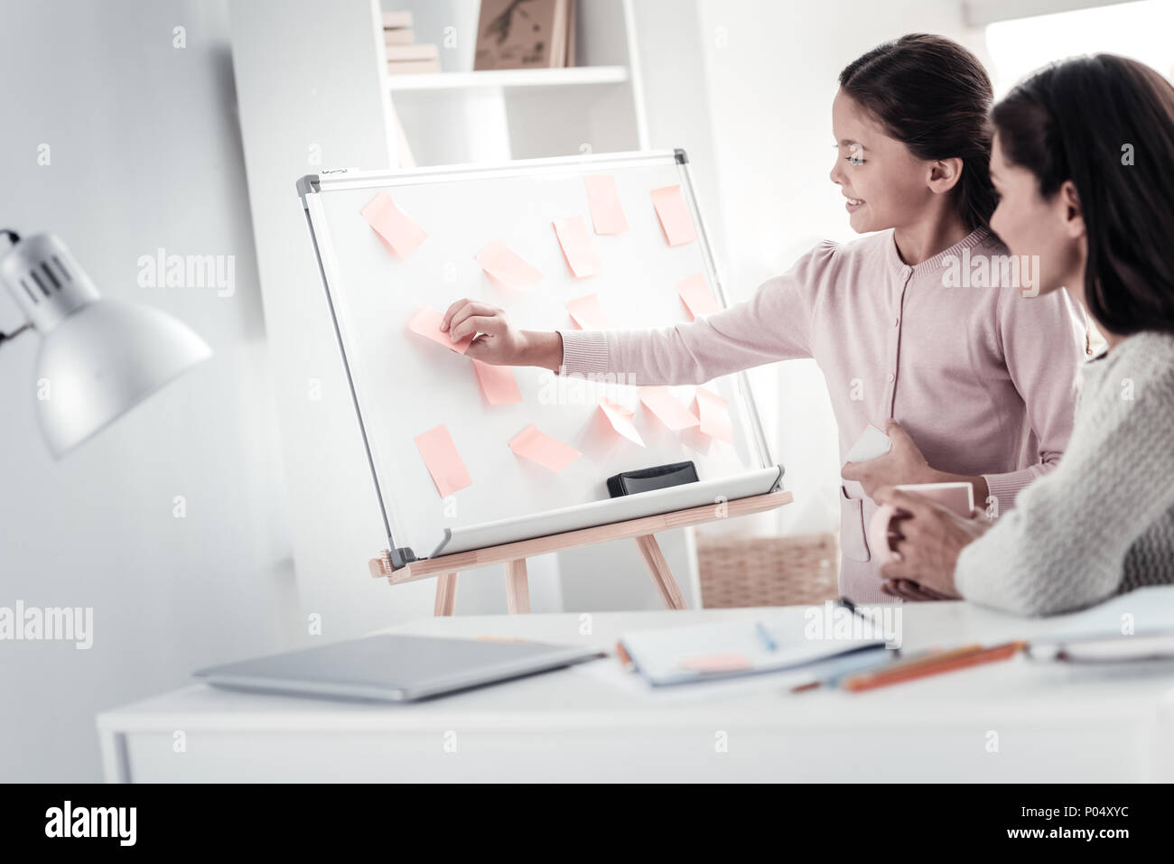 Attentive woman listening to project presentation - Stock Image