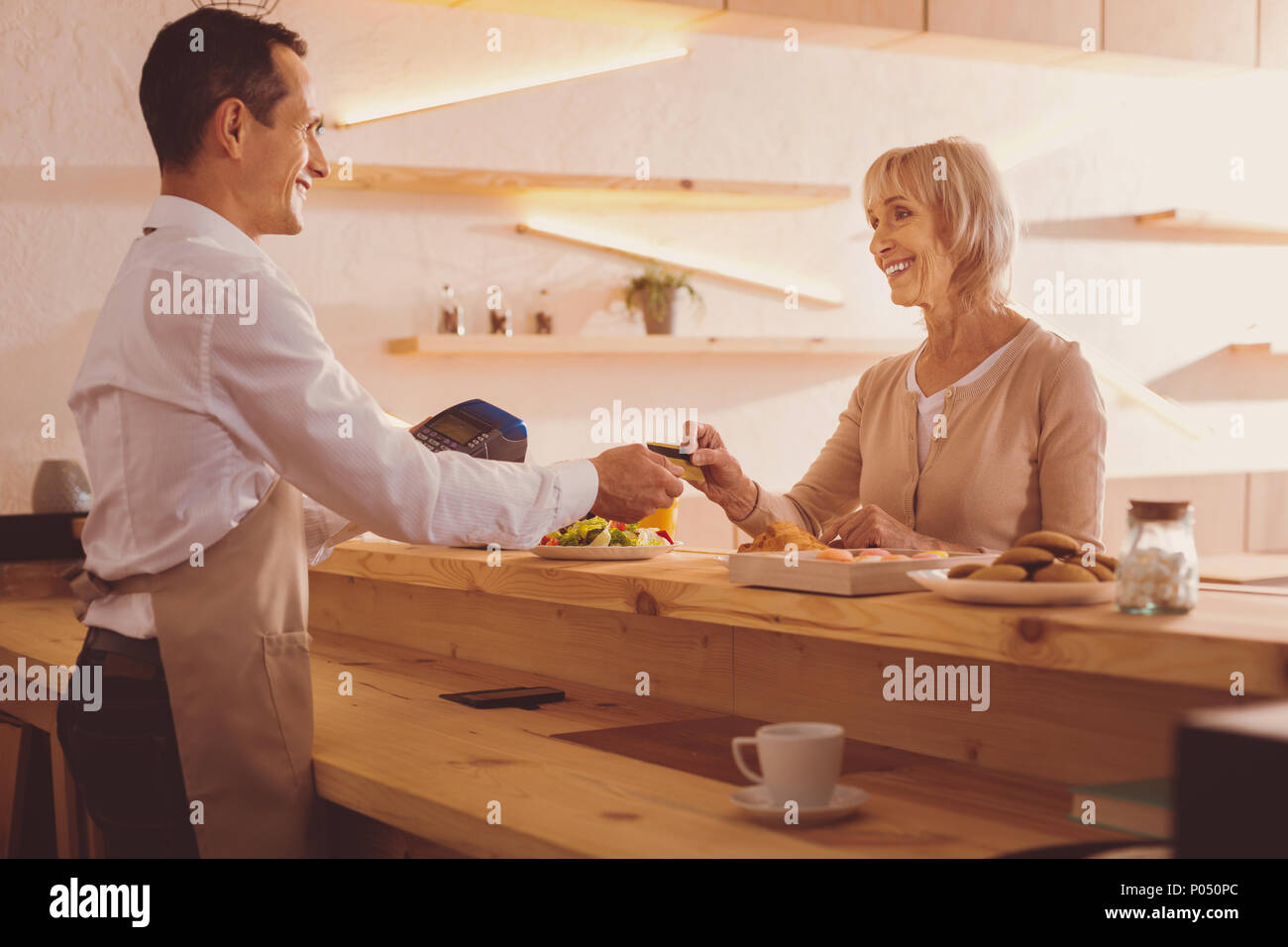 Convenient payment. Pleasant senior woman giving her bank card to the barista, paying for food ordered in cafe, while smiling at him charmingly - Stock Image