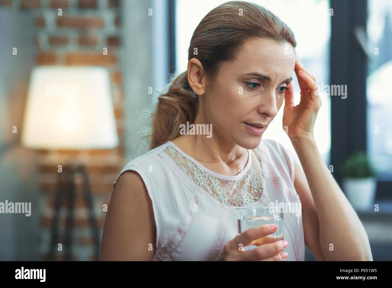 Calm mature woman feeling discomfort - Stock Image