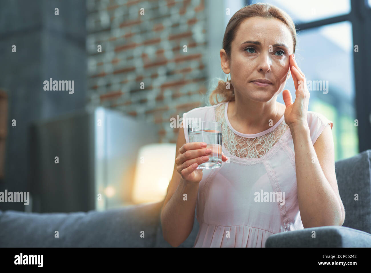 Concentrated mature woman suffering from migraine - Stock Image