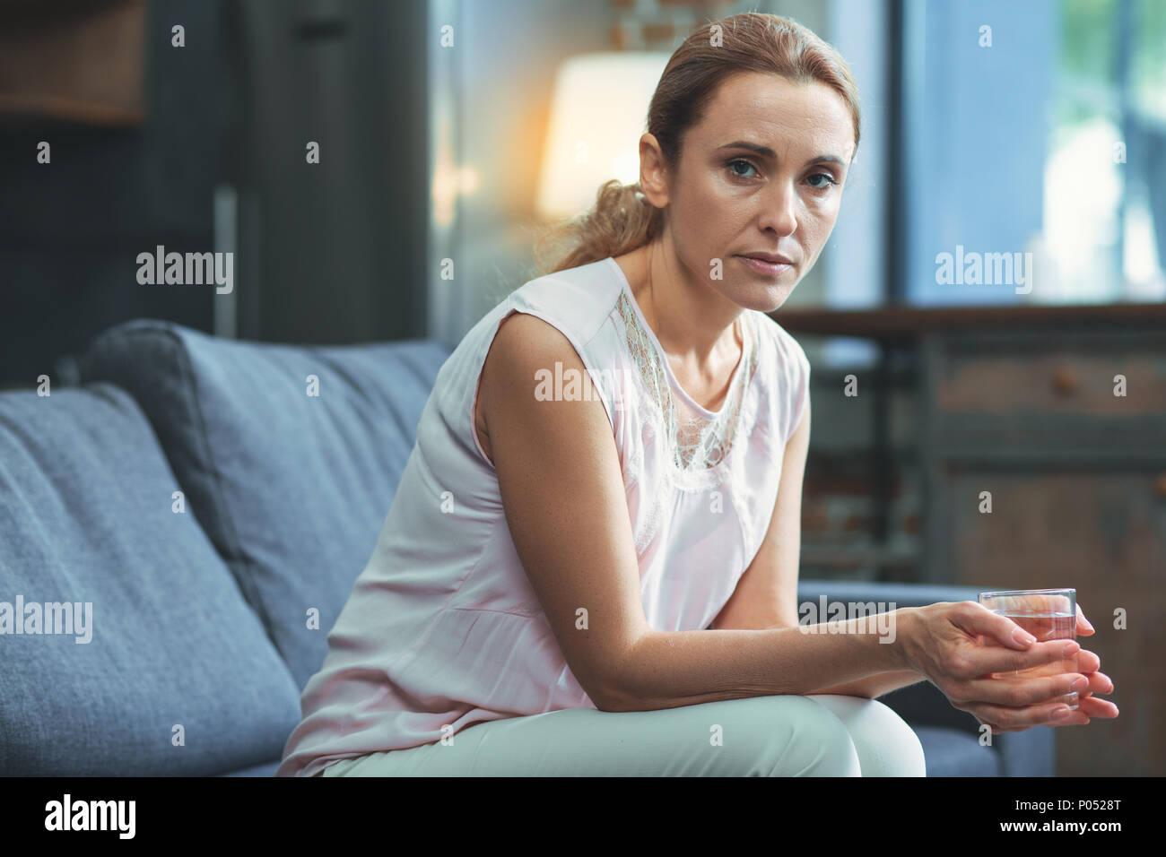 Focused mature woman showing depression symptoms - Stock Image