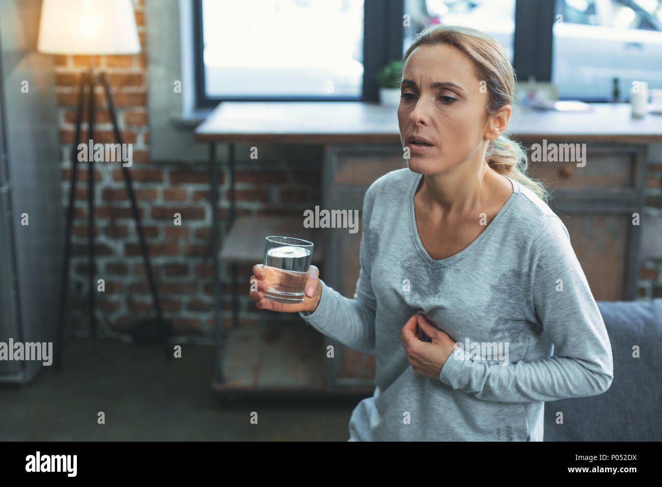 Exhausted mature woman facing menopause - Stock Image