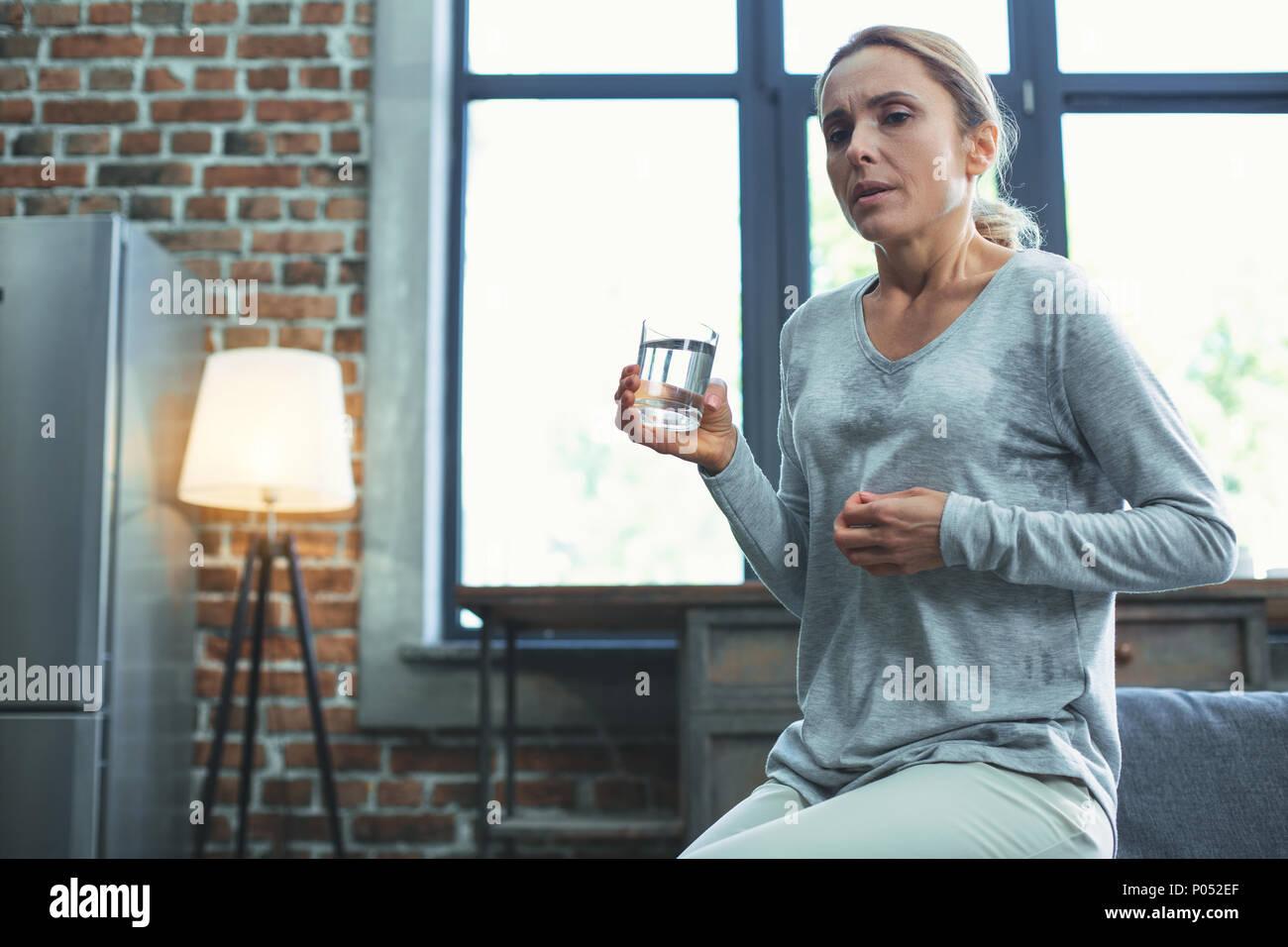 Tired mature woman having menopause symptoms - Stock Image