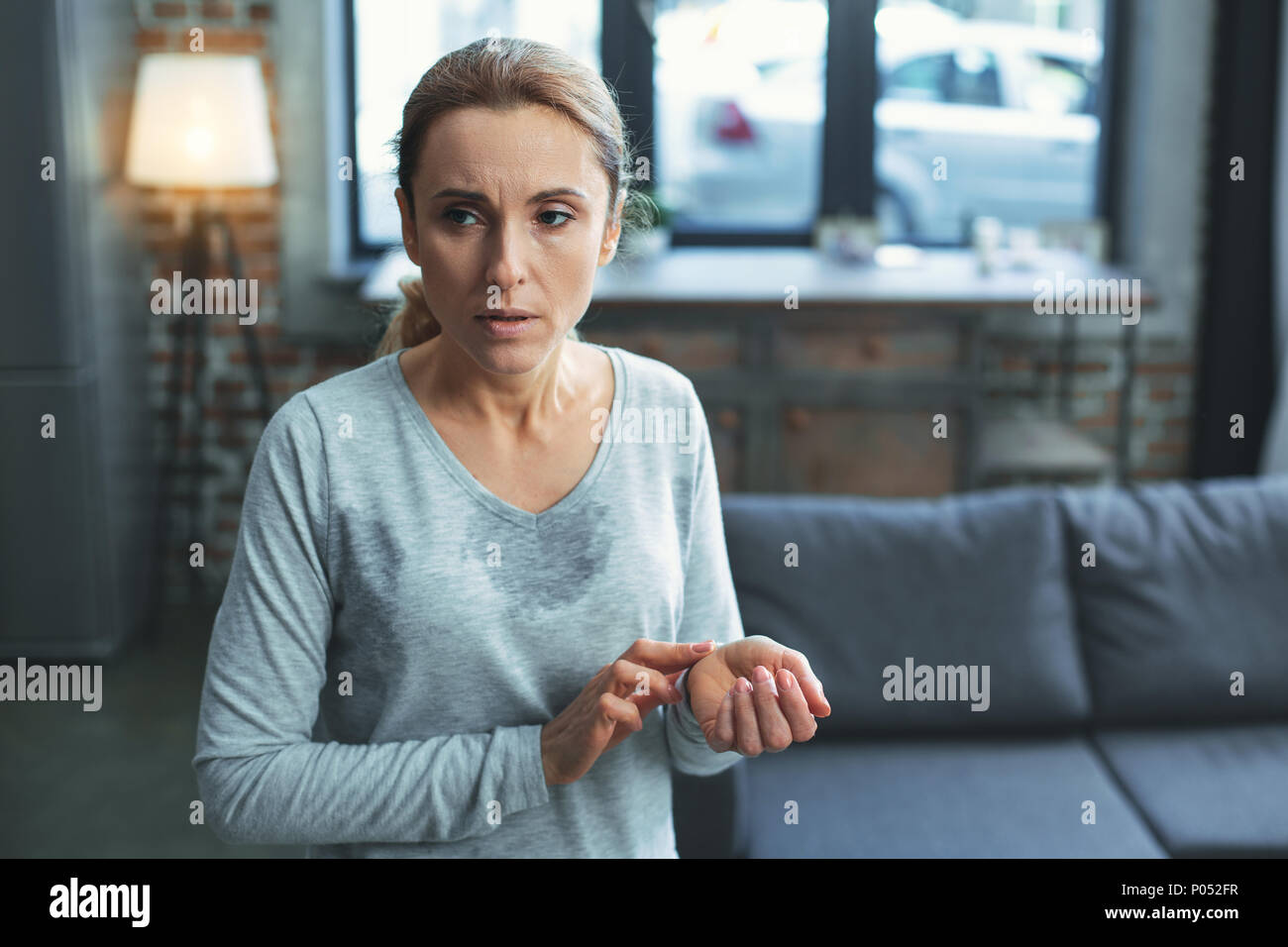 Thoughtful mature woman numbering heartbeat - Stock Image