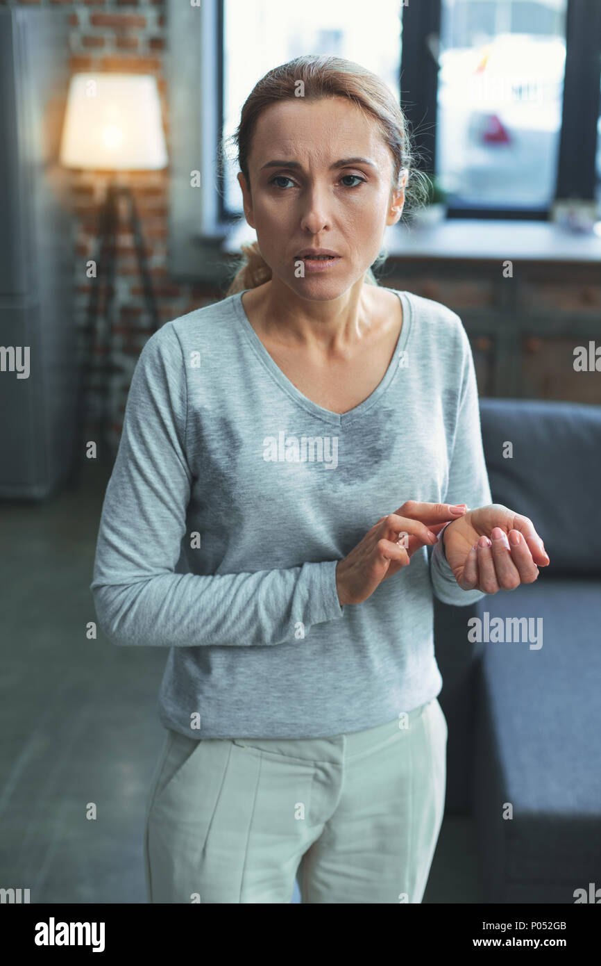 Pleasant mature woman determining heartbeat - Stock Image