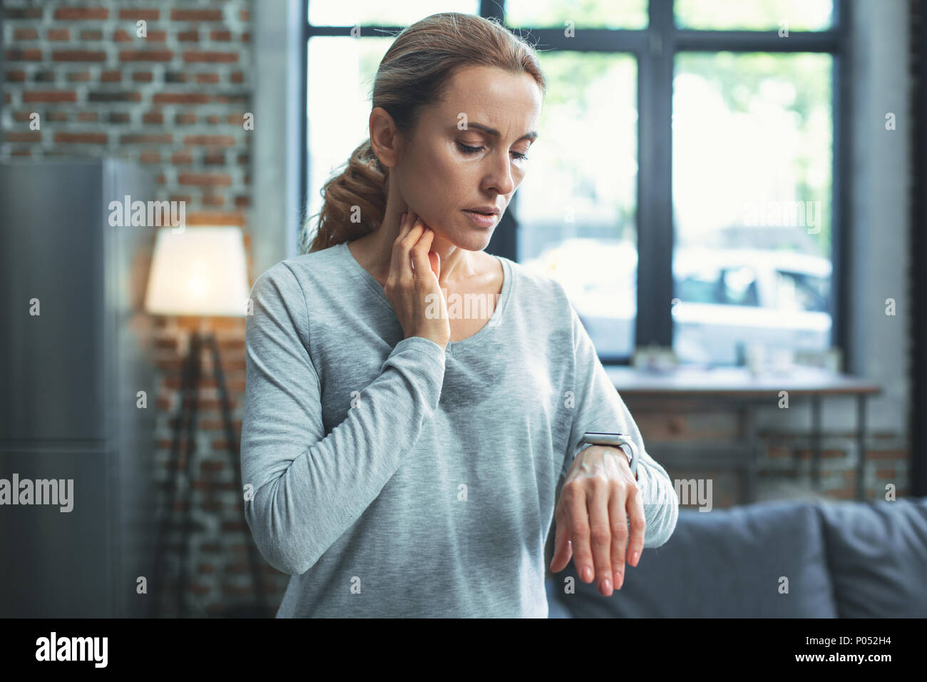 Earnest mature woman checking life signs - Stock Image