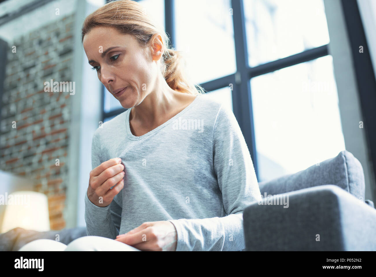 Exhausted mature woman entering menopause - Stock Image