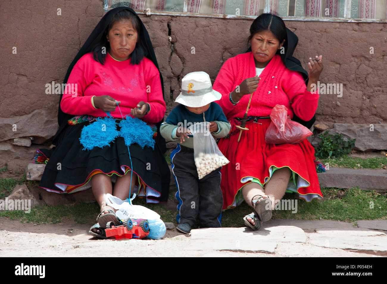 A young child inspects his bag of sweets, while his Mother and another woman spend their afternoon knitting on Taquile island, Lake Titicaca. Peru - Stock Image