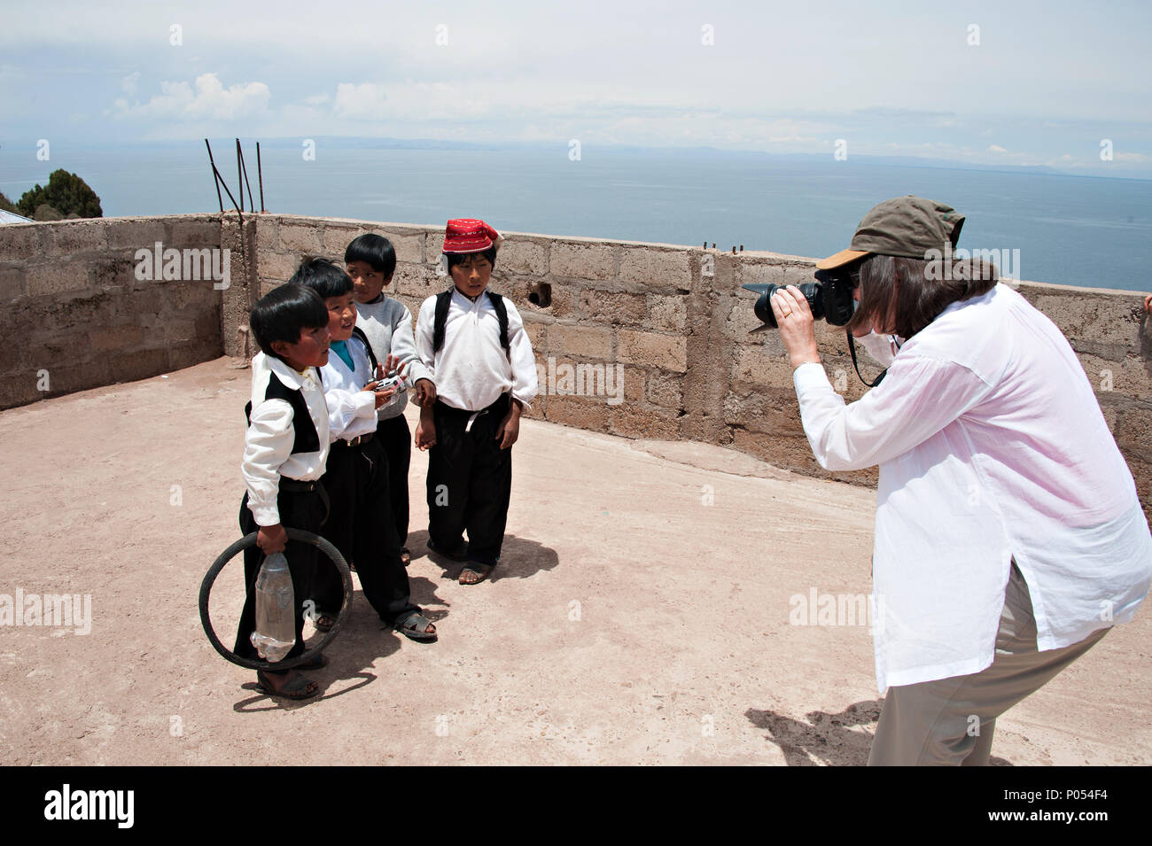 Young boys gather round to pose for a photograph in exchange for candy and sweets in the village at Taquile island, Lake Titicaca. Peru - Stock Image