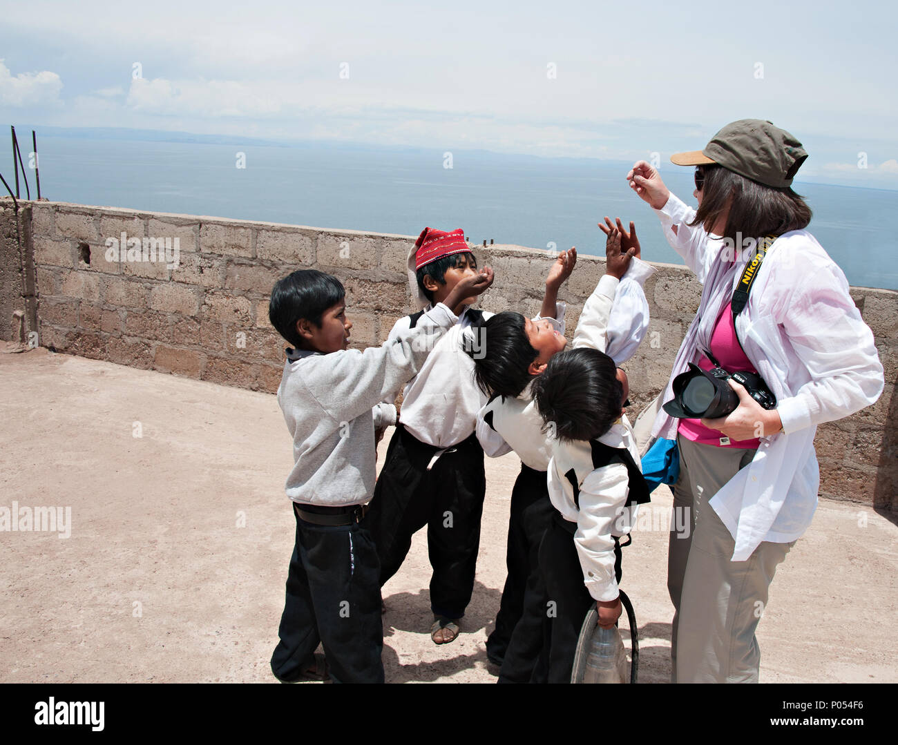 Young boys gather round a tourist offerring candy and sweets in the village at Taquile island, Lake Titicaca. Peru - Stock Image