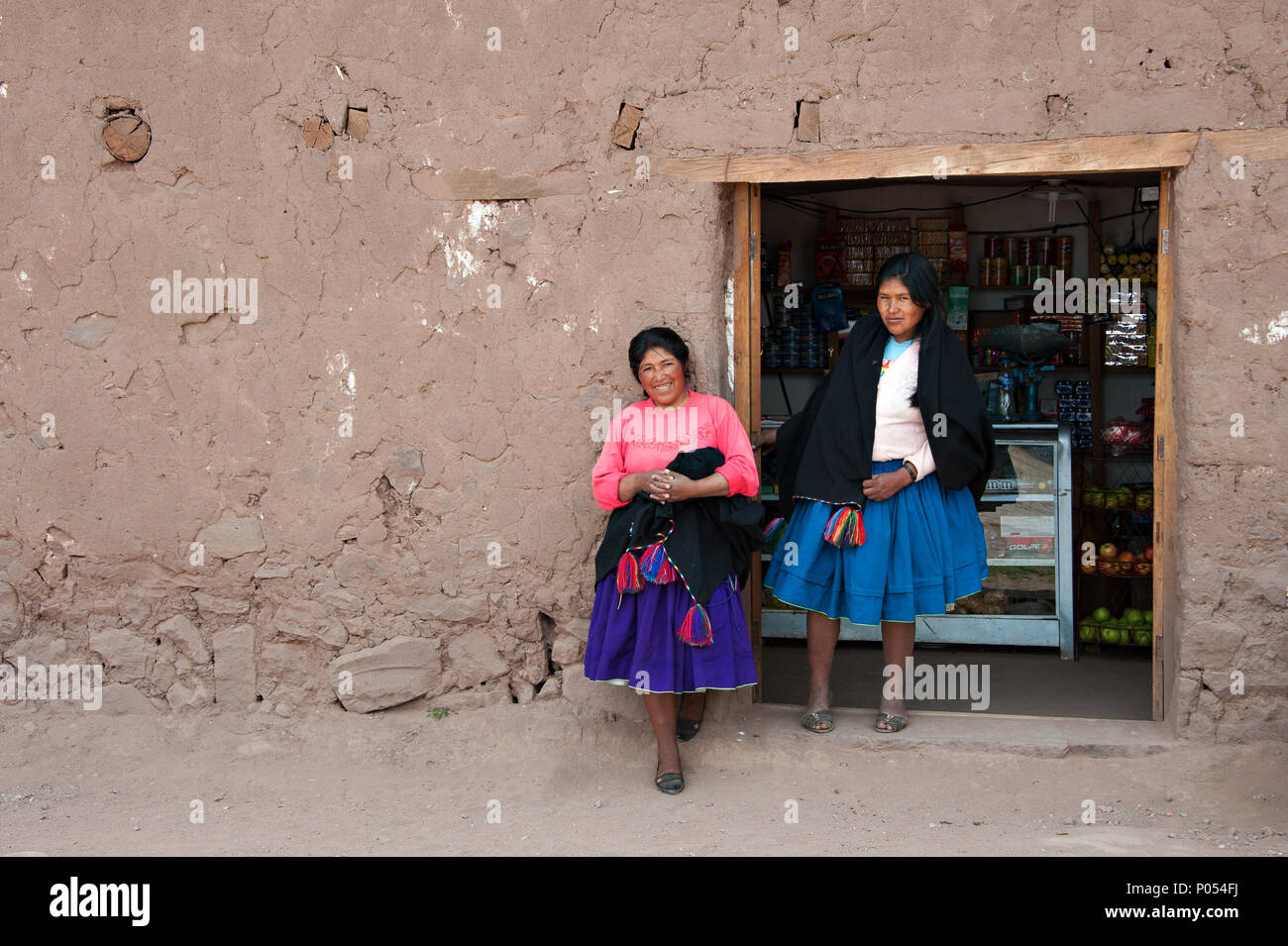 Two local women in traditional peruvian skirts pose for a photograoph outside their shop on Taquile island, Lake Titicaca. Peru - Stock Image