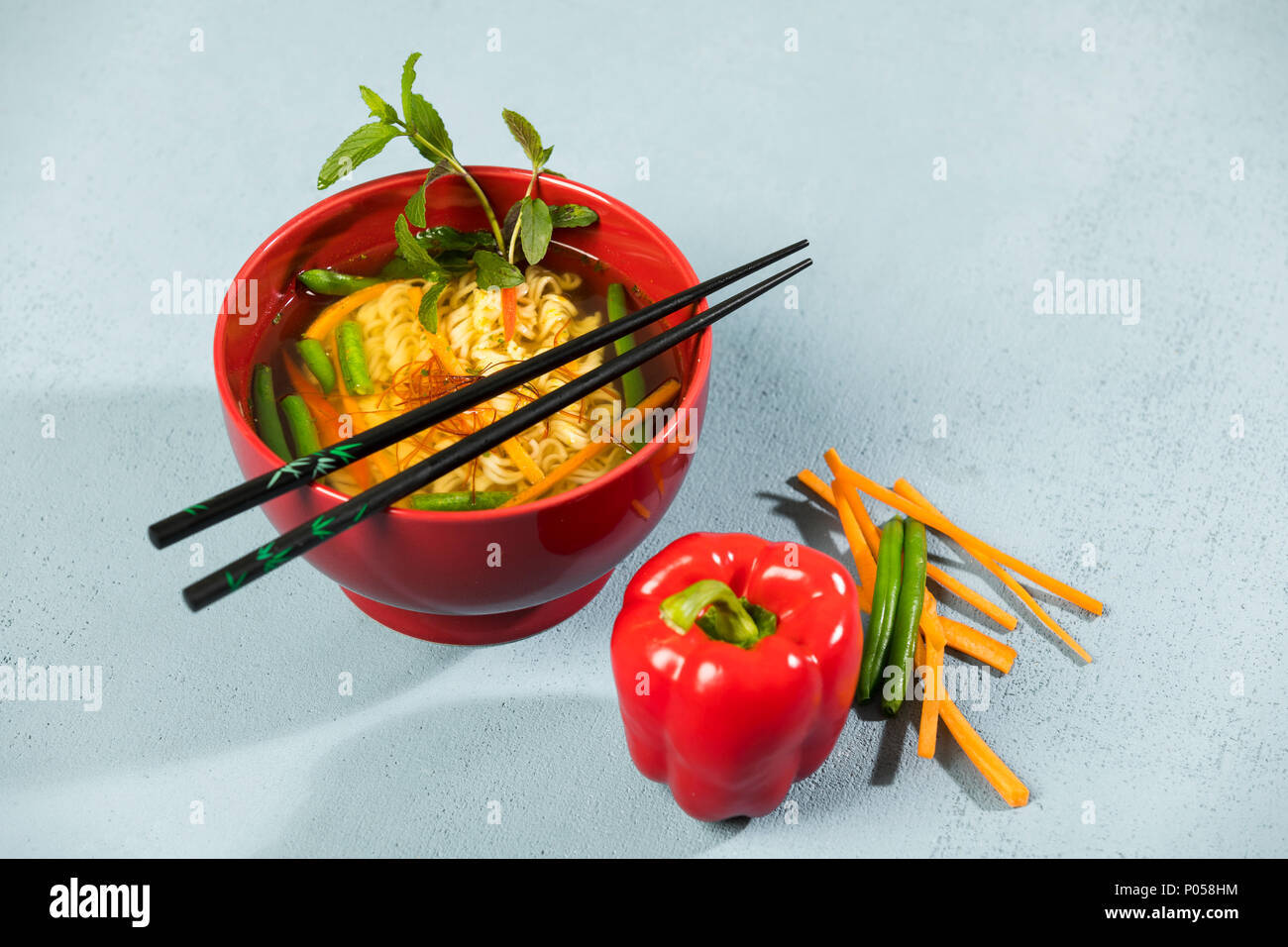 Nudelsuppe mit Mie-Nudeln, Karotten, grüne Bohnen, Paprika, Minze und Chili, Studio Stock Photo