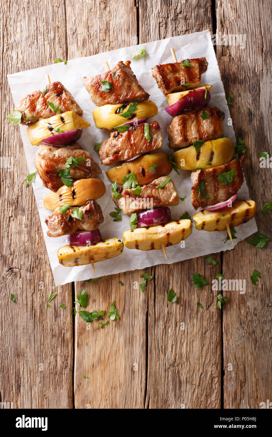 Rustic juicy kebabs of pork with apples and red onions close-up on parchment on the table. Vertical top view from above - Stock Image