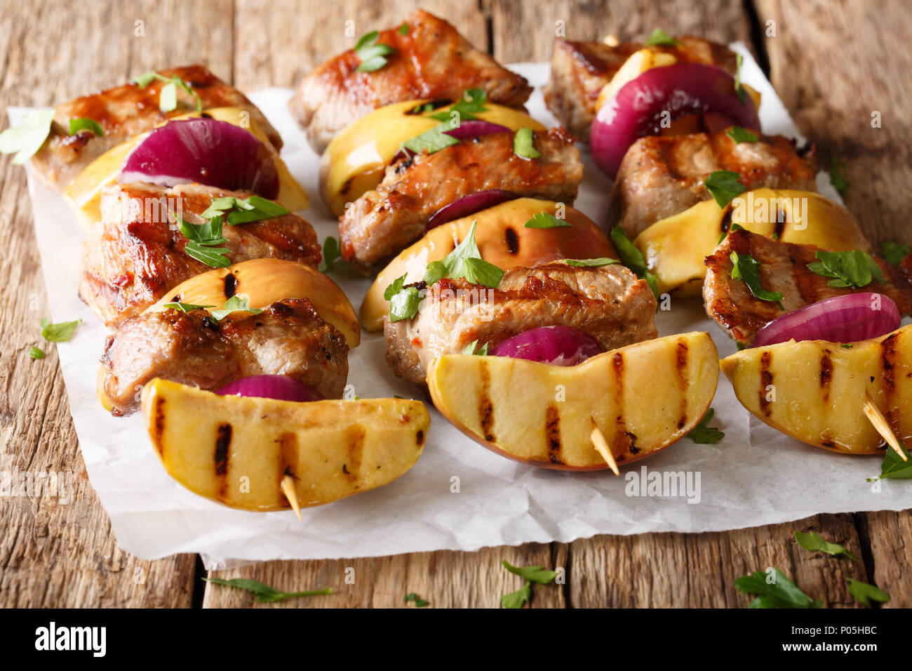 Rustic juicy kebabs of pork with apples and red onions close-up on parchment on the table. horizontal - Stock Image