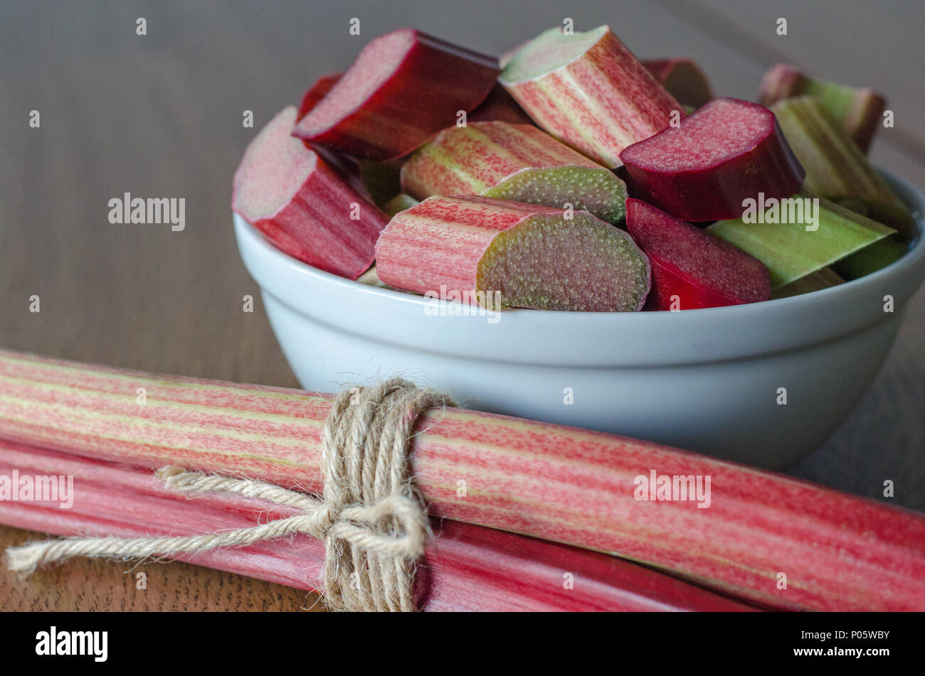 Close-up of slised rhubarb in a bowl on wooden background - Stock Image