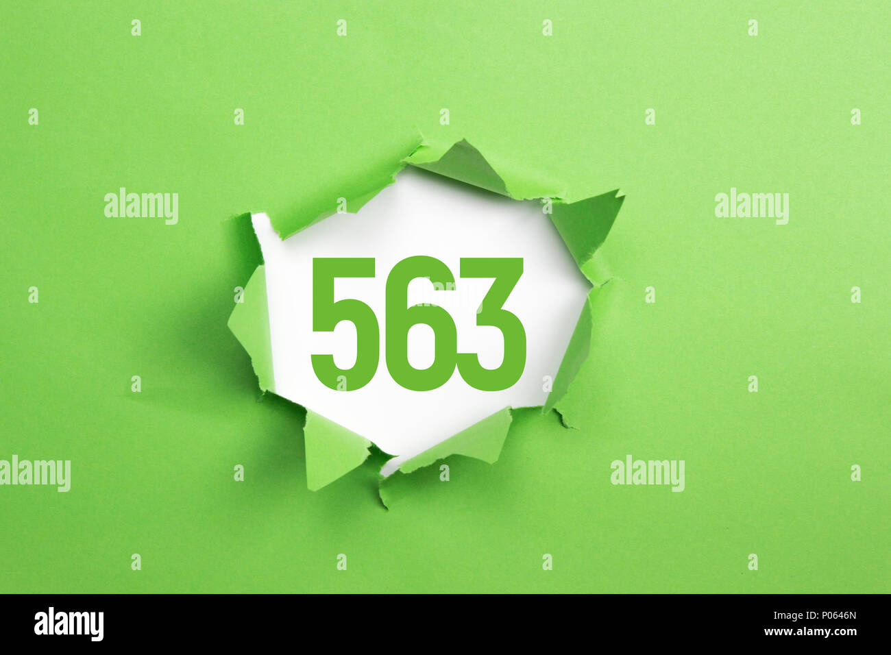 Green Number 563 on green paper background - Stock Image