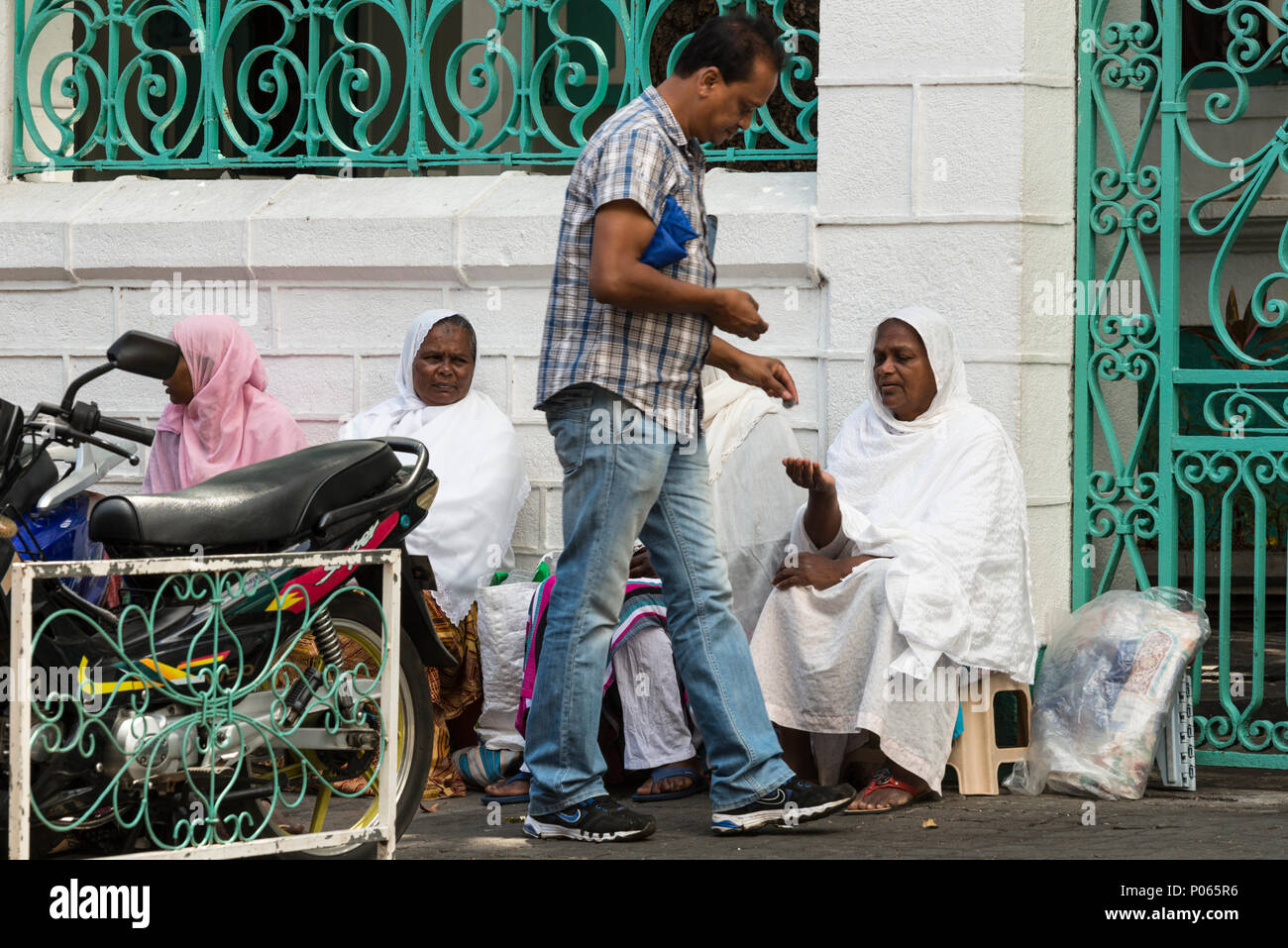 A passerby giving money to one of a group of women sitting on the street waiting for alms outside Jummah Mosque on a Friday, Port Louis,  Mauritius - Stock Image