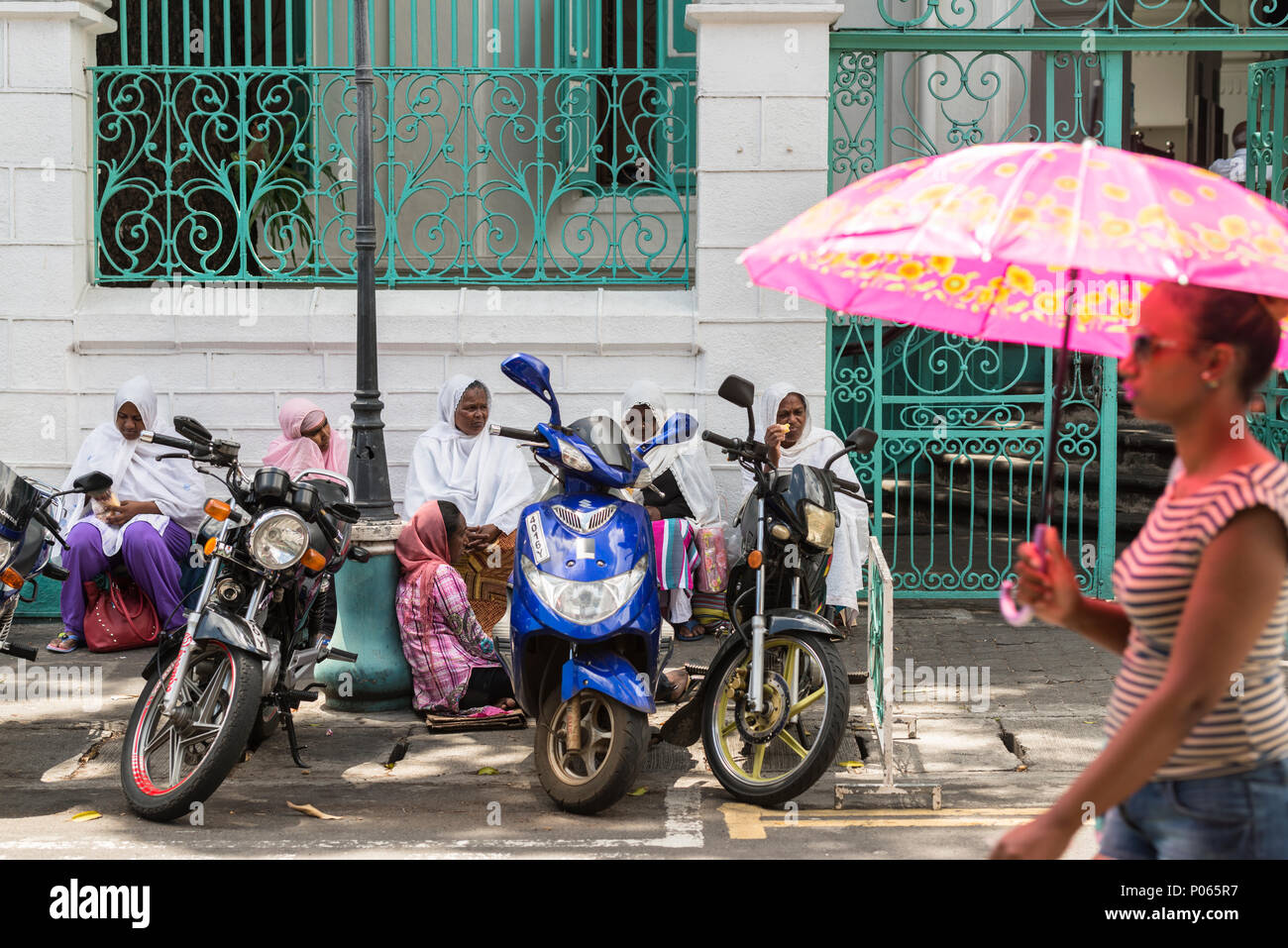 A young woman walking past a group of women sitting on the street waiting for alms outside Jummah Mosque on a Friday, Port Louis,  Mauritius Stock Photo