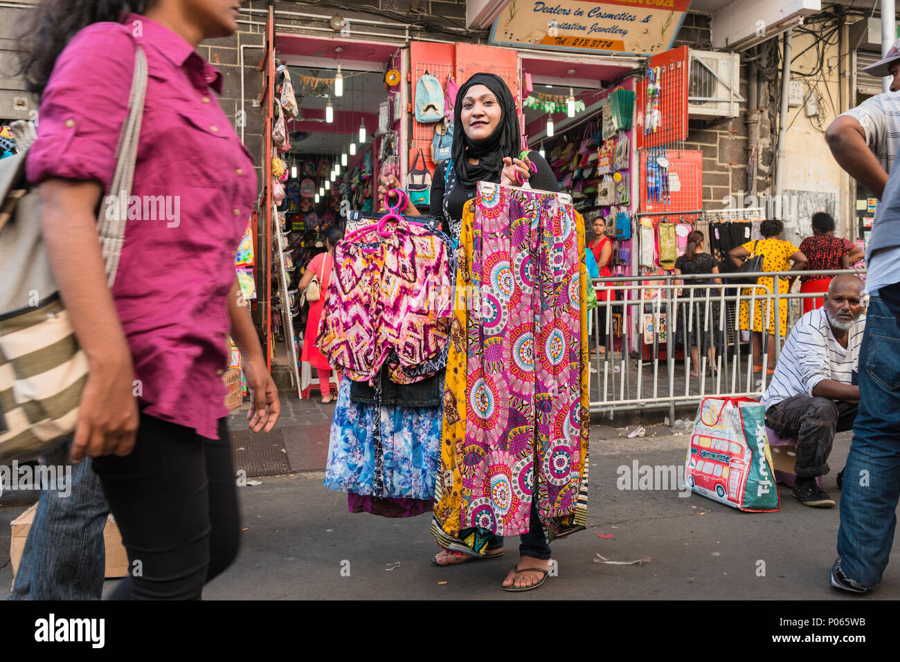 Woman street vendor selling clothes in a street market in downtown Port Louis, Mauritius - Stock Image