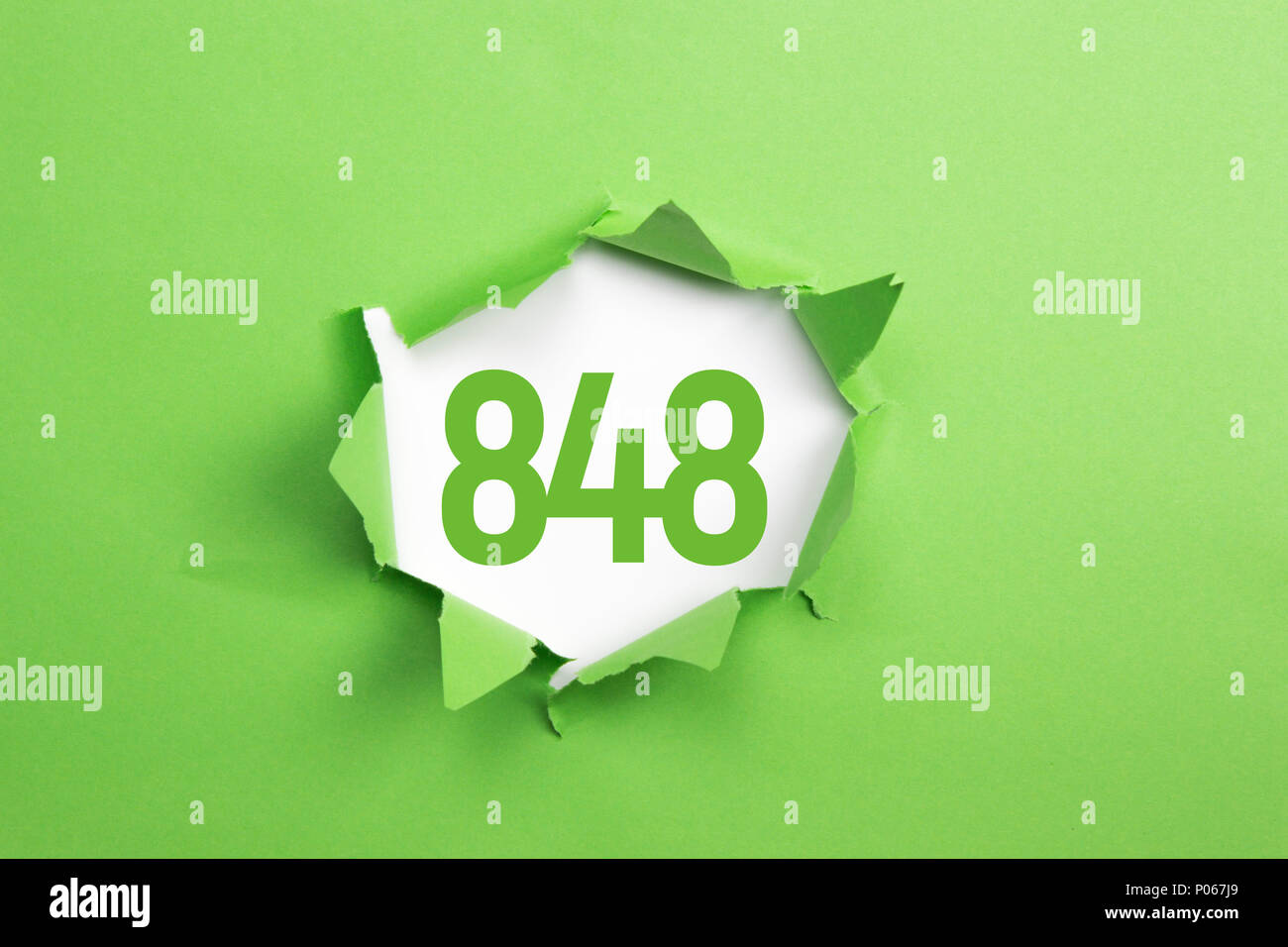 Green Number 848 on green paper background - Stock Image