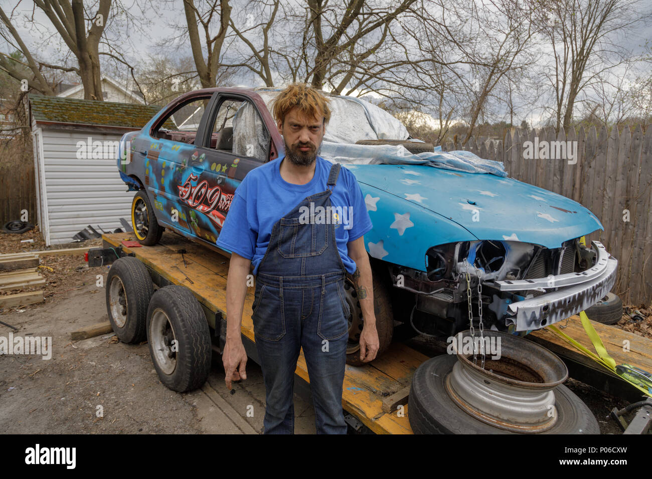Gloversville, New York: A demolition derby driver, and his car. - Stock Image