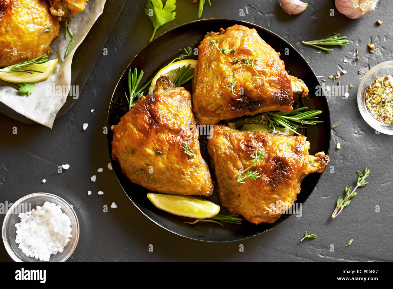 Chicken thighs on plate over black stone background. Top view, flat lay - Stock Image